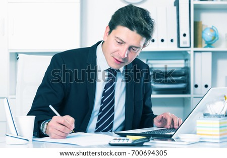 Smiling man working in the office at the laptop with documents