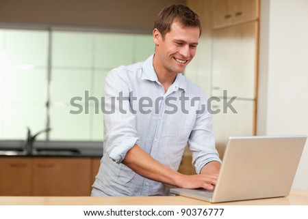 Smiling man working on laptop in the kitchen