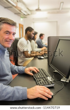 Smiling man working with the computer in class