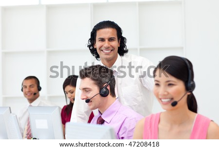 Smiling manager checking his employee's work in a call center
