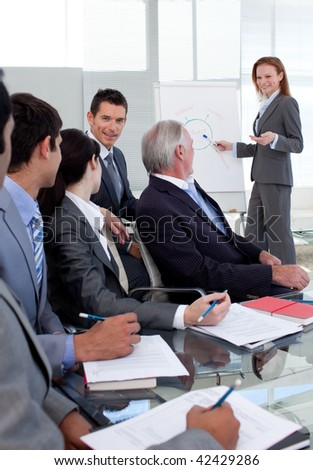 Smiling manager giving a presentation to her team in the office - stock photo