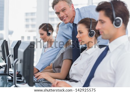 Smiling manager helping call centre employee on her computer - stock photo