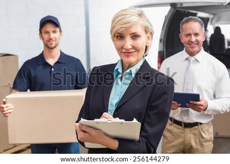 Smiling manager holding clipboard in front of his colleagues in a large warehouse - stock photo