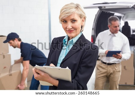 Smiling manager holding clipboard in front of his colleagues in a large warehouse
