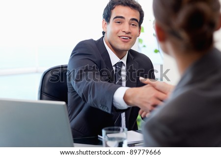Smiling manager interviewing a female applicant in his office - stock photo