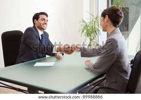 Smiling manager interviewing a good looking applicant in his office - stock photo