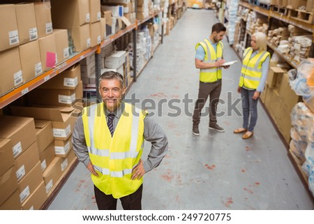 Smiling manager placing his hands on his hips in a large warehouse - stock photo