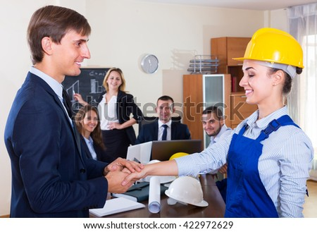 Smiling manager shaking hand of happy female employee at office - stock photo