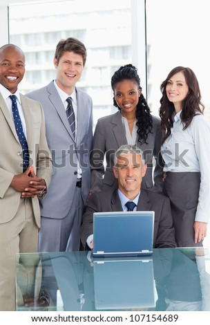 Smiling manager sitting at the desk behind a laptop and surrounded by his team - stock photo