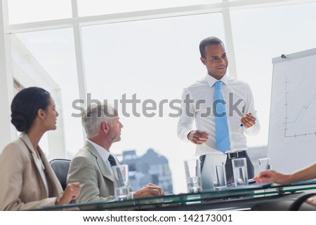 Smiling manager standing in front of colleagues during a presentation - stock photo