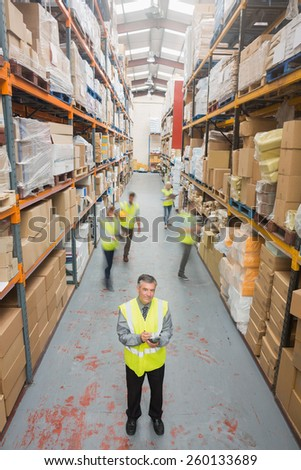 Smiling manager standing in front of his team in warehouse - stock photo