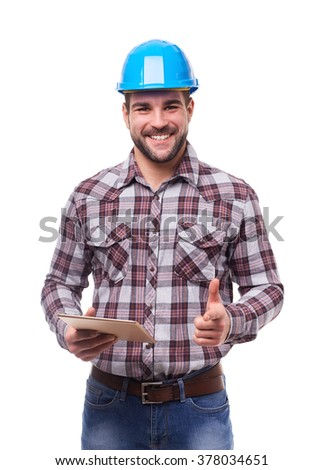 Smiling manual worker in blue helmet and shirt with digital tablet and gesture pointing at you - stock photo