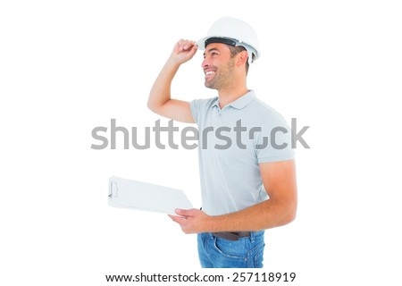 Smiling manual worker wearing hardhat while holding clipboard on white background - stock photo