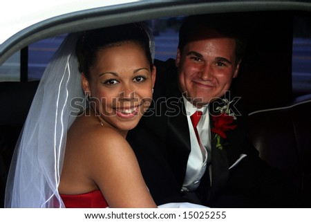 smiling married bi-racial couple in limousine - stock photo