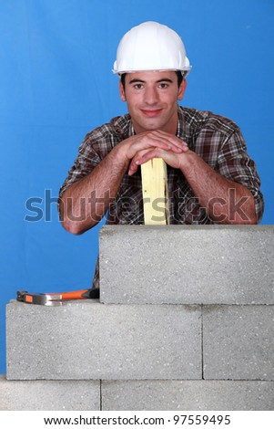 Smiling mason in front of blue background - stock photo