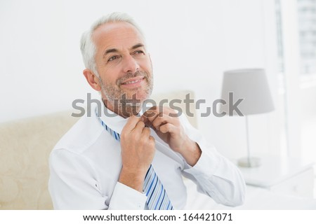 Smiling mature businessman adjusting neck tie at a bright home