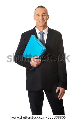 Smiling mature businessman holding a binder. - stock photo