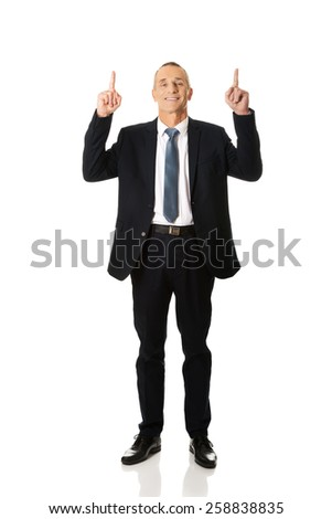 Smiling mature businessman pointing upwards.  - stock photo