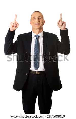 Smiling mature businessman pointing upwards.