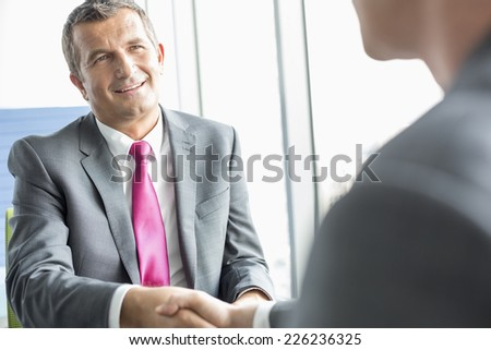 Smiling mature businessman shaking hands with partner in office - stock photo