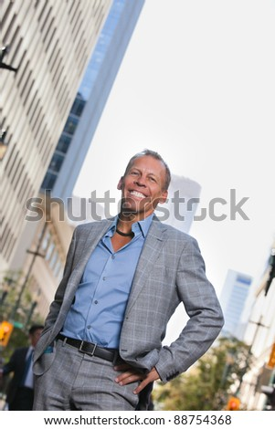 Smiling mature businessman standing with buildings in background - stock photo