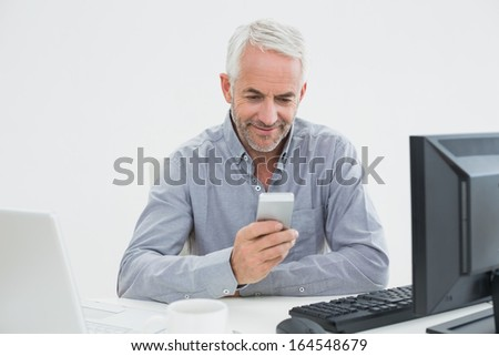 Smiling mature businessman with cellphone, laptop and computer at desk against white background