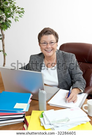 Smiling mature businesswoman at her office desk with phone, laptop computer, etc. - stock photo