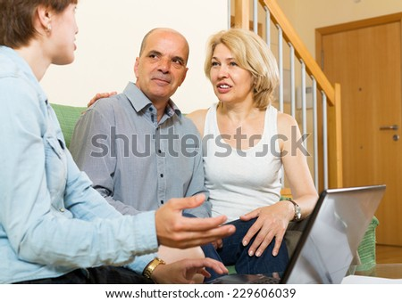 Smiling mature couple discussing for agent or employee of  company at home - stock photo