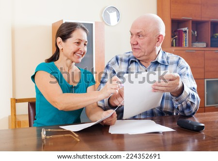 Smiling mature couple reading documents at home interior - stock photo