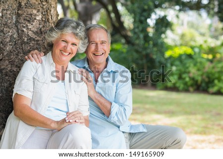 Smiling mature couple sitting together by a tree looking at camera - stock photo