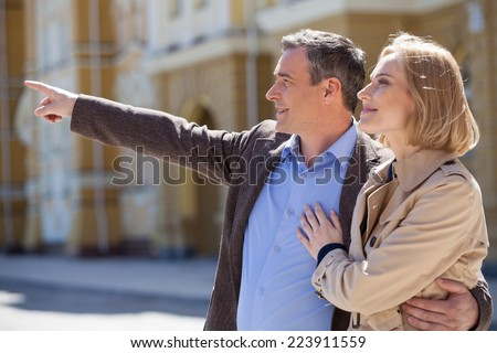 Smiling mature couple standing outside and looking ahead. adult man pointing with finger and hugging woman - stock photo