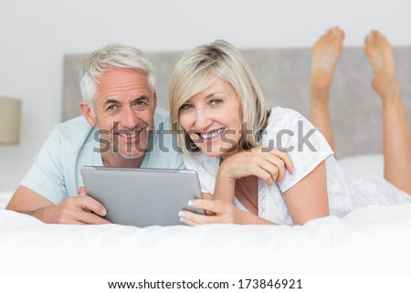 Smiling mature couple using digital tablet in bed at home