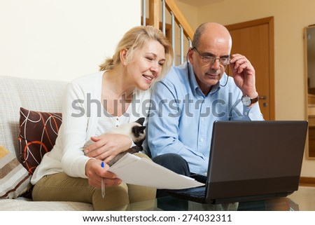 Smiling mature couple with financial documents and laptop in home interior
