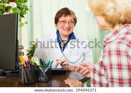 Smiling mature doctor consulting female patient