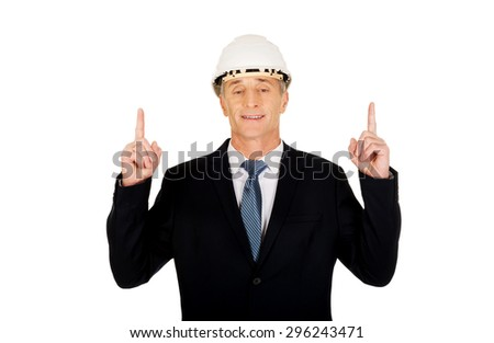 Smiling mature engineer with hard hat pointing up. - stock photo