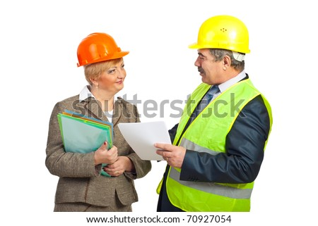 Smiling mature engineers with helmets having conversation and holding folders isolated on white background - stock photo