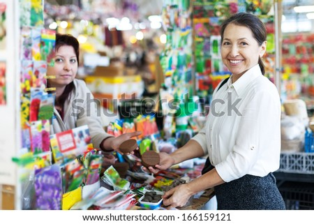 Smiling mature female gardener buys solid fertilizer  at market - stock photo