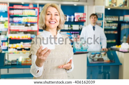 Smiling mature female patient buying medicine in pharmacy   - stock photo