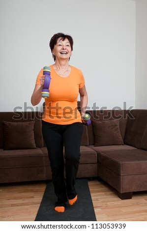 Smiling mature fitness woman exercising with barbells at home - walking - stock photo
