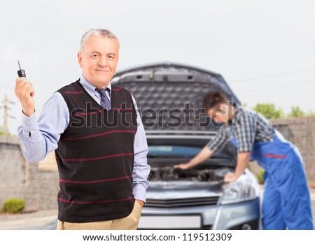 Smiling mature gentleman holding a car key while in the background mechanic is checking his car - stock photo