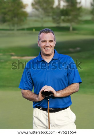 Smiling Mature Golfer on golf course - stock photo
