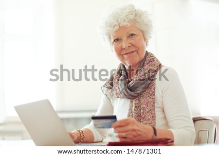 Smiling mature lady holding a credit card in front of her laptop - stock photo