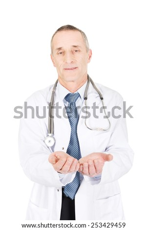 Smiling mature male doctor with open hands. - stock photo