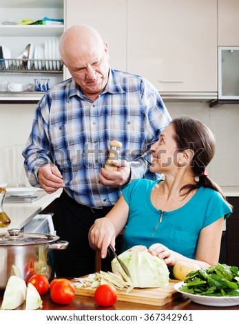 Smiling mature man and  woman cooking lunch together in domestic  kitchen - stock photo