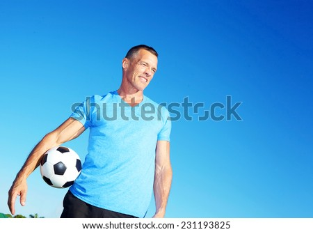 Smiling mature man holding football against clear blue sky - stock photo
