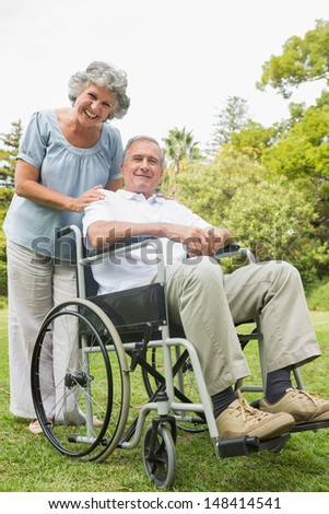 Smiling mature man in wheelchair with partner looking at camera in park - stock photo