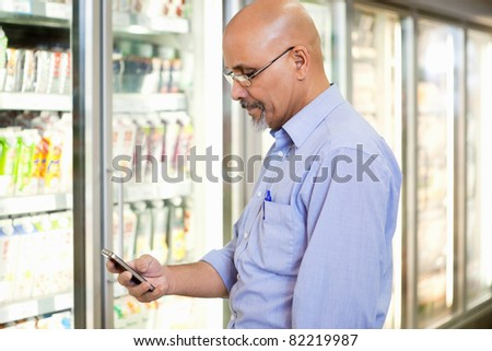 Smiling mature man looking at mobile phone while standing in front of refrigerator in supermarket - stock photo