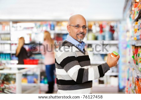 Smiling mature man shopping in the supermarket with people in the background - stock photo
