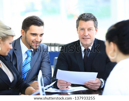 Smiling mature man sitting at a business meeting with colleagues - stock photo