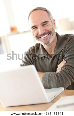 Smiling mature man sitting in front of laptop - stock photo